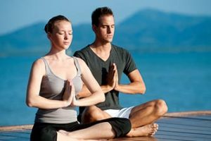 Pareja-haciendo-yoga-junto-al-mar